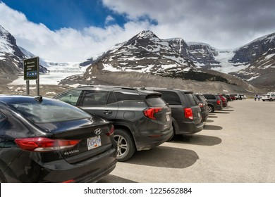 COLUMBIA ICEFIELD, ALBERTA, CANADA - JUNE 2018: Cars parked at the Columbia Icefield Visitor centre in Alberta, Canada. The Athabasca Glacier is in the background.