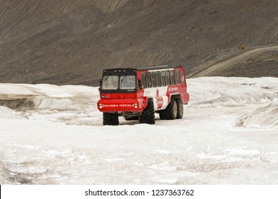COLUMBIA ICEFIELD, ALBERTA, CANADA - JUNE 2018: Massive six wheel purpose-built vehicle taking tourists onto the Athabasca Glacier in the Columbia Icefield in Alberta, Canada.