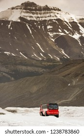 COLUMBIA ICEFIELD, ALBERTA, CANADA - JUNE 2018: Huge six wheel purpose-built vehicle taking tourists onto the Athabasca Glacier in the Columbia Icefield in Alberta, Canada.