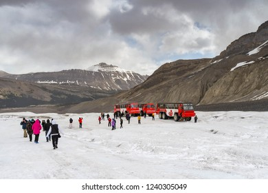 COLUMBIA ICEFIELD, ALBERTA, CANADA - JUNE 2018: Tourists getting out of a massive six wheel purpose-built vehicle on the Athabasca Glacier in the Columbia Icefield in Alberta, Canada.