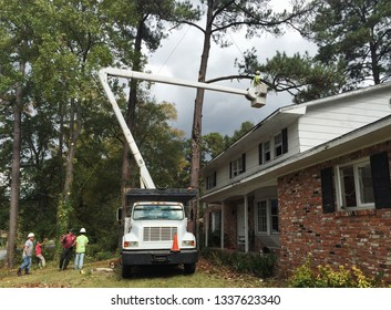 COLUMBUS, GA/USA Oct 28, 2015: Landscaper and subcontractors working on a real property improvement project by removing trees close to the residential home before a new roof can be installed.