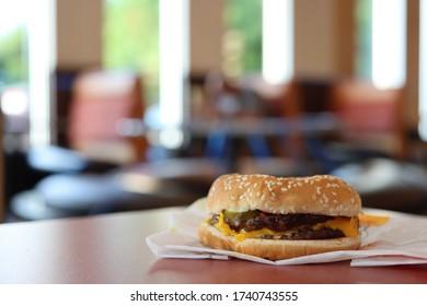 COLUMBUS, GEORGIA/ USA - 05-20-2020 Cheeseburger at a Burger King restaurant. Out of focus restaurant interior as backdrop.