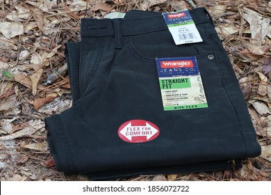 COLUMBUS, GEORGIA/ USA - 08-06-2020 Black pair of Wrangler jeans lying on fall leaves outdoors.