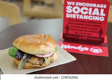 COLUMBUS, GEORGIA/USA - 05-24-2020 Grilled Chicken Sandwich a Wendy's. Sign on table encouraging social distancing.