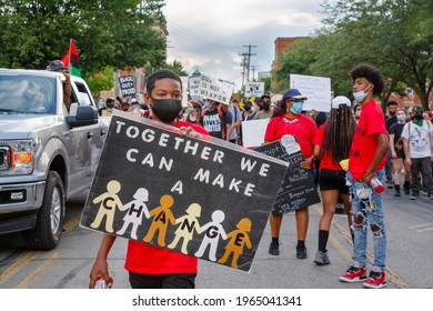 COLUMBUS, OH - APRIL 22, 2021: Young boy stands at front of peaceful protest march holding up a sign