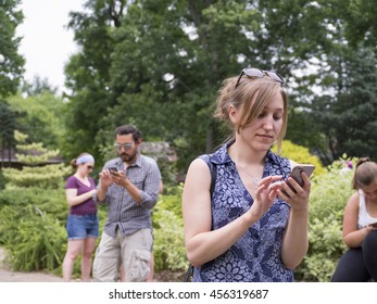 COLUMBUS, OHIO, USA- JULY 21: 2016: Millennials play Pokemon Go at the Columbus, Ohio Park of Roses. The location-based augmented reality mobile game by Niantic Labs launched in early July 2016.