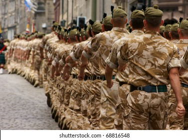A column of British Army soldiers marching in desert camouflage.