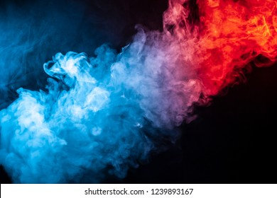 A column of colored smoke of blue and red color from a wap of an abstract form tending upwards on a black isolated background.