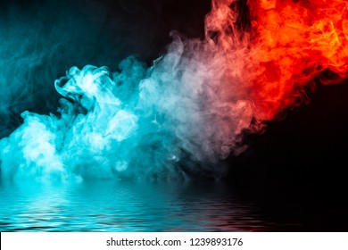 A column of colored smoke of green and red color from a wap of an abstract form tending upwards on a black isolated background above a river with small waves.