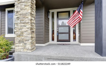 Column porch of luxurious house with American flag.  Northwest, USA