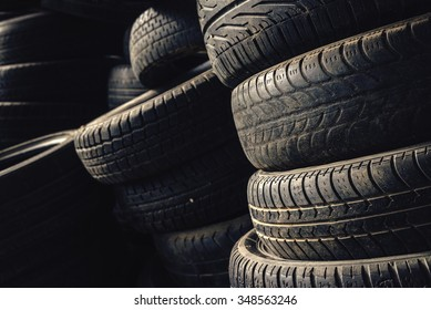 Column stack of old used car tires in secondary car parts shop garage.