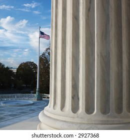 Column of Supreme Court building with American flag in Washington D.C.