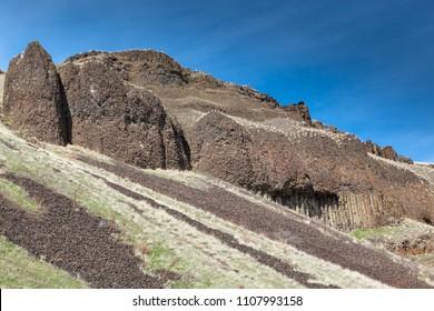 Columnar basalt rocks form a steep hillside with erosion creating falling gravel in Lyons Ferry State Park in Eastern Washington.