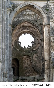 The columned, pointed arched vault and circular ornamental stone window of the ruined church of the Zámbék monastery. It was built around 1220 in the late Romanesque - early Gothic style.
