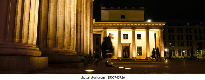 Columns of the Brandenburg Gate And part of the square in front of them. With people. Brandenburg Gate at night in golden light. Elements of Greek architecture. Built as a symbol of peace.