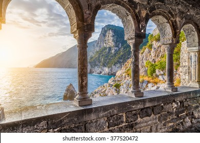 Columns of famous gothic Church of St. Peter (Chiesa di San Pietro) with beautiful shoreline scenery at sunset in the town of Porto Venere, Ligurian Coast, province of La Spezia, Italy