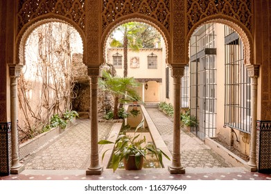 Columns located at the monument of the Alhambra, is a pond and plants on the sides