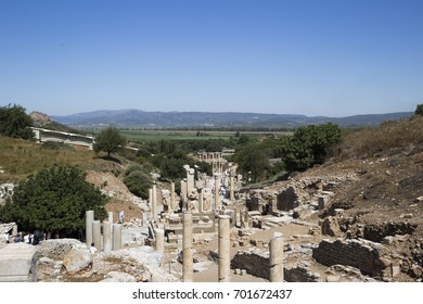 Columns and ruins of the ancient city of Ephesus between the hills overgrown with dry grass and trees against the blue sky