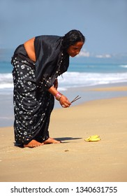 COLVA BEACH, GOA, INDIA - NOVEMBER 24, 2007: Unidentified Hindu pilgrim carries out a religious ceremony on the coast of the Arabian sea