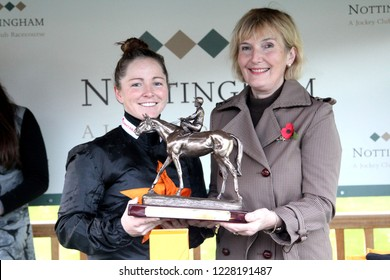 COLWICK PARK, NOTTINGHAM, UK : 7 November 2018 - Miss Becky Smith holds aloft the 2018 Lady Amateur Jockeys Championship Trophy after being presented by Sarah Oliver at Nottingham Racecourse