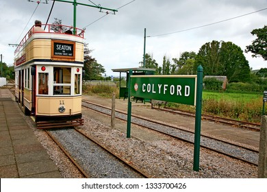 Colyford England May 2018. Electric tram destined for Seaton arriving at Colyford station. Yellow white livery. Open top deck with passengers seated. Green station name sign. Overhead electric wires.