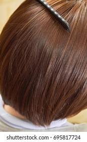 Comb brushing female hair. Brown hair close up.