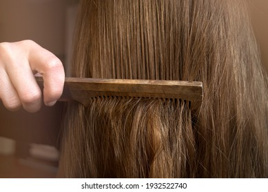 Comb your hair. Young woman combing her hair with long blond hair.
