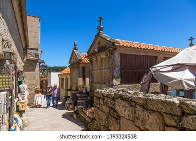 COMBARRO, SPAIN - JUN 15, 2017: Tourists walk along the street with traditional horreo barns.
