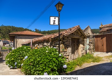 COMBARRO, SPAIN - JUN 15, 2017: Old outbuildings and information center sign