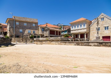 Combarro, Spain. Landscape of the old town with a traditional Orreo barn and a stone cross