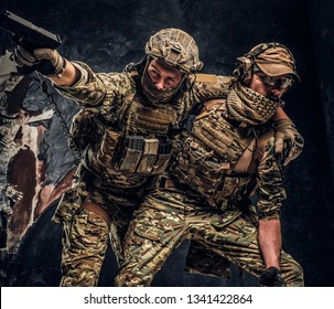Combat conflict, special mission, retreat. The military soldier carrying teammate while he shoots back. Studio photo against a dark wall