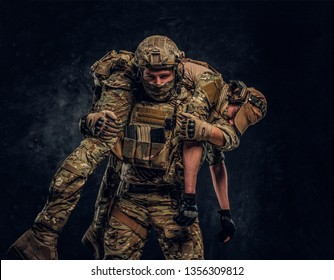 Combat conflict, special mission, retreat. Soldier special forces rescue his wounded teammate carrying him on his shoulders from the battlefield. Studio photo against a dark wall