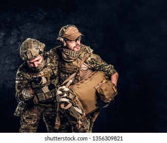 Combat conflict, special mission, retreat. Military medic rescues his wounded teammate carrying him off the battlefield. Studio photo against a dark wall