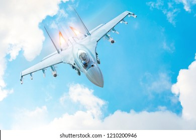 Combat fighter jet on a military mission with weapons - rockets, bombs, weapons on wings, with fire afterburner engine nozzles, flies in clouds