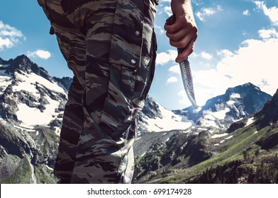 Combat knife in hand the soldier the commando in the background of snow-capped peaks in the mountains. Scout with a knife. Tourist backpacker holds the knife in the wild.