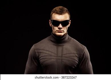 Combat muscled action hero man wearing brown sweater and sunglasses. Studio shot.
