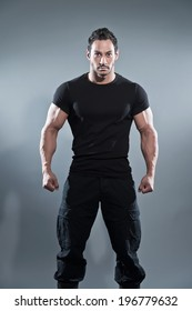 515780581db8a Combat muscled fitness man wearing black shirt and pants. Studio shot  against grey.