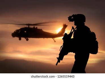 Combat ready special operation forces soldier with helicopter in sunset