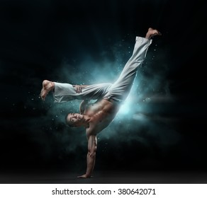 combative sport: male fighter trains capoeira on a black background