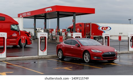 COMBER, CANADA - April 16, 2019: Tesla Supercharger Station with red Tesla Model S plugged-in, charging and truck stop in the background.