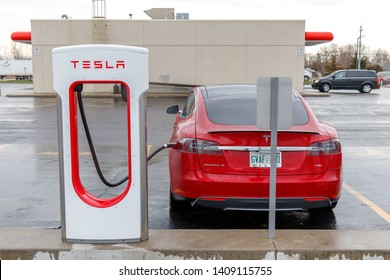 COMBER, CANADA - April 16, 2019: Tesla Supercharger Stall with red Tesla Model S plugged-in, charging.