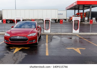 COMBER, CANADA - April 16th, 2019: Red Tesla Model S plugged-in, supercharging at designated parking, marked with Tesla logo at Tesla's Comber location.