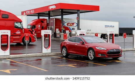 COMBER, CANADA - April 16th, 2019: Red Tesla Model S supercharging at Tesla's Comber location with truck stop in background.