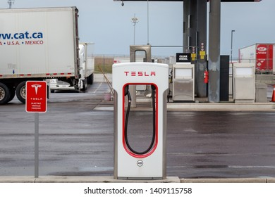 COMBER, CANADA - April 16th, 2019: Tesla Supercharger Stall with gas station and truck stop in background.