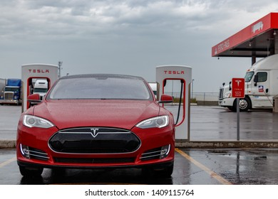 COMBER, CANADA - April 16th, 2019: Front of Tesla Model S at Tesla Supercharger Station in the rain, with truck stop seen behind.