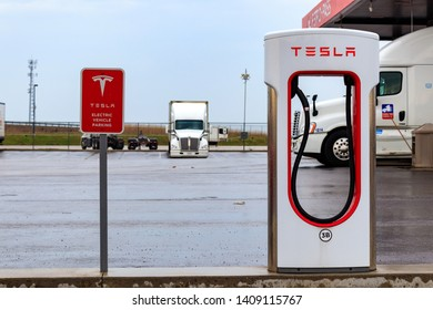 "COMBER, CANADA - April 16th, 2019: Tesla Supercharger Stall and ""Tesla Electric Vehicle Only"" sign with truck-stop in background."