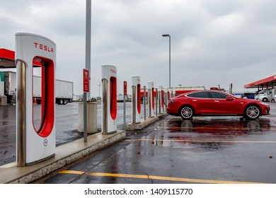 COMBER, CANADA - April 16th, 2019: Tesla Supercharger Station with Tesla Model S charging in the rain.