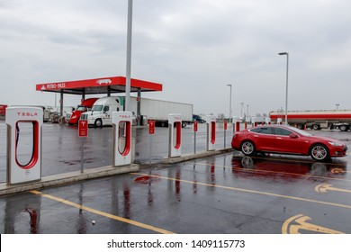 COMBER, CANADA - April 16th, 2019: Tesla Supercharger Station with Model S charging, truck-stop in the background.