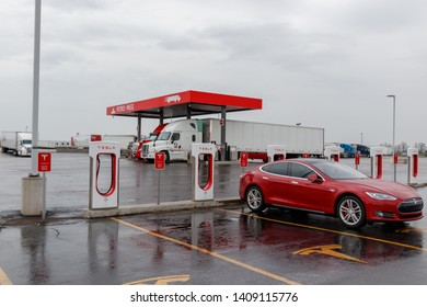COMBER, CANADA - April 16th, 2019: Tesla Supercharger Station with red Model S charging, truck-stop in the background.