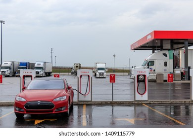 COMBER, CANADA - April 16th, 2019: Tesla Model S plugged-in, supercharging with gas station in the background.